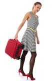 Donna in scarpe rosse del tacco alto che portano una valigia immagine stock libera da diritti