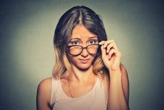 Donna scettica confusa che vi esamina con la disapprovazione Fotografia Stock