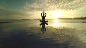 Donna sconosciuta che medita su spiaggia fotografia stock