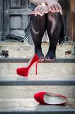 Donna sconosciuta che si siede sopra i punti con le sue scarpe fuori fotografia stock libera da diritti