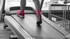 Donna sconosciuta con le scarpe rosa che corre nel rosa spaccato bl della pedana mobile Fotografia Stock