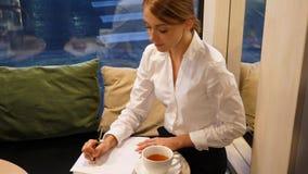 Donna scrivere penna a sfera sul foglio di carta bianco archivi video