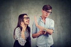Donna seccante che prova a distrarre giovane uomo bello che manda un sms sullo smartphone Fotografia Stock Libera da Diritti