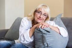 Donna senior adorabile in occhiali che si appoggiano un cuscino Fotografia Stock Libera da Diritti