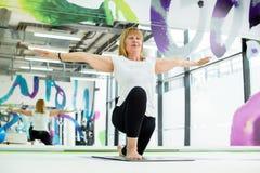Donna senior alla classe di yoga immagine stock