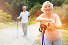 Donna senior allegra che se la appoggia pali di camminata Fotografia Stock Libera da Diritti