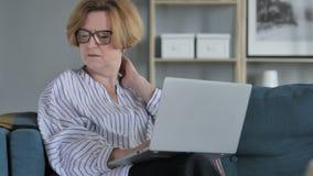 Donna senior anziana con dolore al collo che lavora al computer portatile archivi video