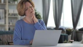 Donna senior anziana stanca con dolore al collo che lavora al computer portatile video d archivio