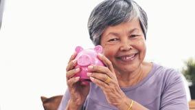 Donna senior asiatica allegra che scuote porcellino salvadanaio che sorride alla macchina fotografica Ritratto dei soldi di rispa stock footage