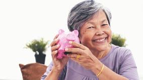 Donna senior asiatica allegra che scuote porcellino salvadanaio che sorride alla macchina fotografica Ritratto dei soldi di rispa video d archivio