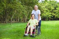 Donna senior asiatica che si siede su una sedia a rotelle con il suo marito Immagini Stock