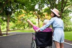 Donna senior asiatica in sedia a rotelle con poca ragazza del bambino che sostiene nonno disabile sulla camminata della natura ve immagine stock libera da diritti
