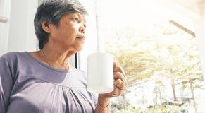 Donna senior asiatica sola infelice con una tazza di caffè sola a casa immagine stock libera da diritti