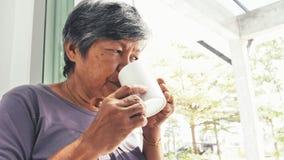 Donna senior asiatica sola infelice con una tazza di caffè sola a casa, movimento lento video d archivio