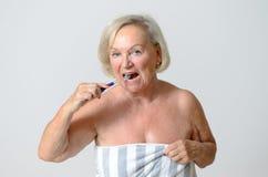 Donna senior avvolta in asciugamano che pulisce i suoi denti Fotografia Stock