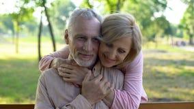 Donna senior che abbraccia marito dietro, riunione romantica nel parco, flirt e divertimento immagine stock libera da diritti