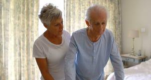 Donna senior che aiuta uomo senior a camminare con il camminatore in camera da letto stock footage