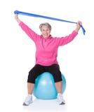 Donna senior che allunga esercitando attrezzatura Fotografia Stock Libera da Diritti