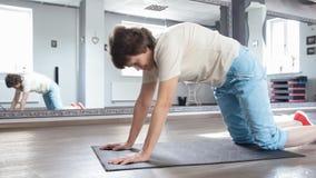 Donna senior che allunga fuori nella stanza di forma fisica, esercizio di yoga archivi video