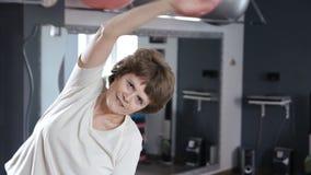 Donna senior che allunga fuori nella stanza di forma fisica, matura, esercizio, yoga video d archivio