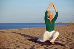 Donna senior che allunga sulla spiaggia Fotografie Stock