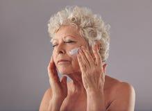 Donna senior che applica crema antinvecchiamento sul suo fronte Fotografie Stock Libere da Diritti