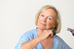 Donna senior che asciuga col phon i suoi capelli biondi Fotografia Stock Libera da Diritti
