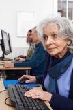 Donna senior che assiste alla classe del computer immagine stock