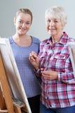 Donna senior che assiste alla classe della pittura con l'insegnante fotografie stock