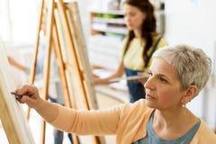 Donna senior che attinge cavalletto allo studio della scuola di arte Fotografie Stock