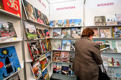 Donna senior che cerca un libro in uno scaffale per libri Fotografia Stock