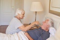Donna senior che dà medicina al suo marito malato a letto immagini stock