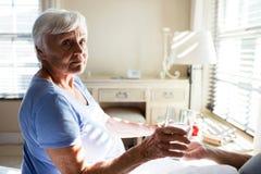 Donna senior che dà medicina all'uomo senior nella camera da letto Fotografie Stock