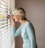 Donna senior che dà una occhiata ai ciechi fotografie stock