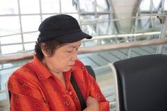 Donna senior che dorme su una sedia all'aeroporto Fotografia Stock Libera da Diritti