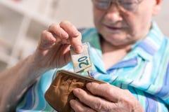Donna senior che elimina una banconota dal suo portafoglio Fotografie Stock