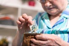 Donna senior che elimina una banconota dal suo portafoglio Fotografie Stock Libere da Diritti