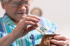 Donna senior che elimina una banconota dal suo portafoglio Immagine Stock Libera da Diritti