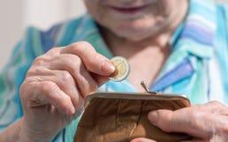 Donna senior che elimina una moneta dal suo portafoglio Fotografia Stock Libera da Diritti