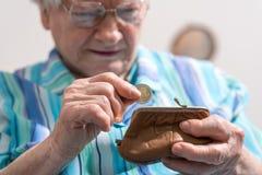 Donna senior che elimina una moneta dal suo portafoglio Immagine Stock