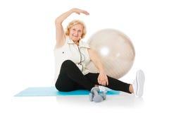 Donna senior che fa allungando esercizio sulla stuoia Immagine Stock Libera da Diritti