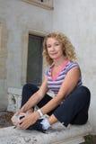 Donna senior che fa allungando gli esercizi in campagna Fotografia Stock