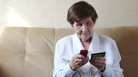 Donna senior che fa attività bancarie online dalla carta di credito sul suo telefono cellulare a casa stock footage