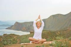 Donna senior che fa gli esercizi di yoga Immagine Stock