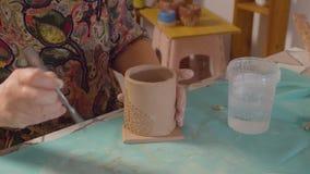 Donna senior che fa la tazza dell'argilla archivi video
