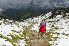 Donna senior che fa un'escursione attraverso le montagne di Snowy, Austria Immagine Stock