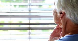 Donna senior che guarda fuori dalla finestra stock footage