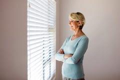 Donna senior che guarda i ciechi fotografie stock