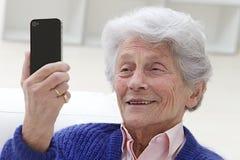 Donna senior che guarda qualcosa al suo telefono cellulare immagini stock libere da diritti