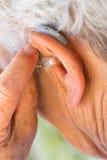 Donna senior che inserisce la protesi acustica in sue orecchie Fotografie Stock